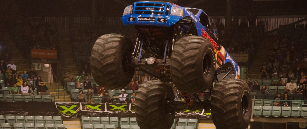 A blue monster truck doing a jump